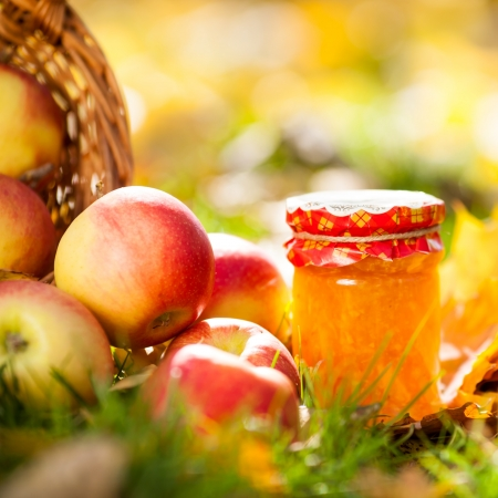 strew: Jam in glass jar and red juicy apples on a grass. Autumn harvest concept Stock Photo