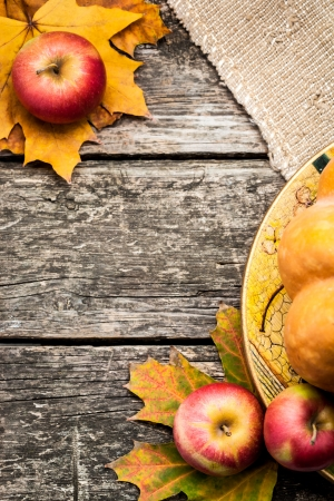 Autumn frame from apples and maple leaves on old wooden table. Thanksgiving day concept photo