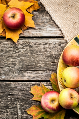 autumn harvest: Autumn border from apples and maple leaves on wooden table. Thanksgiving day concept
