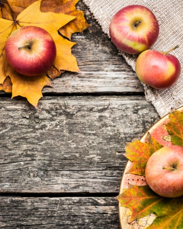 Autumn frame from apples and leaves on old wooden table. Thanksgiving day concept photo