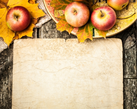 Autumn background from apples and maple leaves on wooden table. Vintage paper blank with copyspace