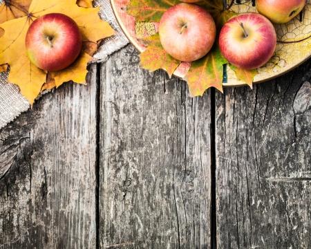 aratás: Őszi határ alma és a lehullott levelek a régi fából készült asztal. Hálaadás napja koncepció