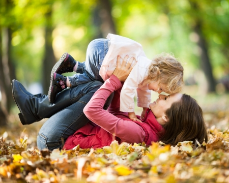 fall fun: Happy family playing against blurred autumn leaves background Stock Photo