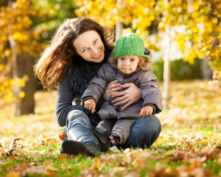 Happy family playing against blurred yellow leaves background in autumn park Stock Photo - 13881871