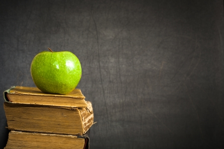 Green apple on old book against blackboard with space for text Back to school!. School concept Stock Photo