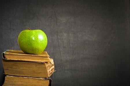 """escuelas: Verde manzana en el viejo libro contra la pizarra con espacio para el texto """"Volver a la escuela!"""". Escuela de concepto"""