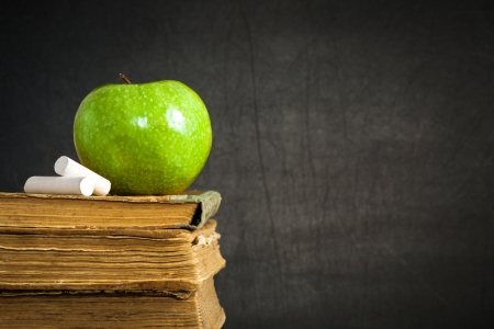 Green apple and chalk on old books against blackboard with space for text. School concept photo