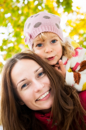 Low angle view of happy smiling family against blurred autumn leaves background Stock Photo - 13881778