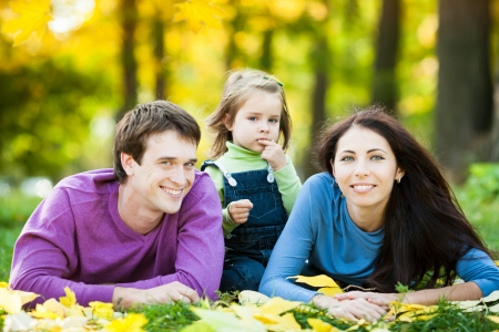 Happy family lying against blurred leaves background in autumn park Stock Photo - 13881665