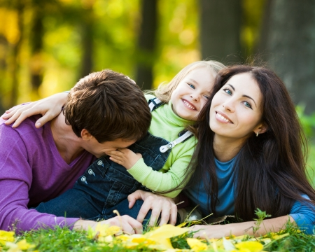 Happy family having fun against blurred autumn leaves background Stock Photo - 13881868