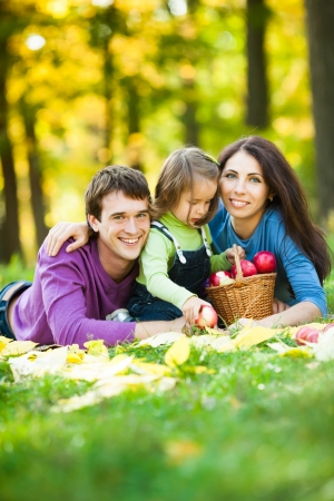 Happy family having picnic against blurred autumn leaves background photo