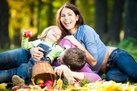Happy family having fun in autumn park  Focus on man photo