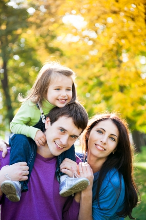 family park: Happy family playing piggyback in autumn park Stock Photo