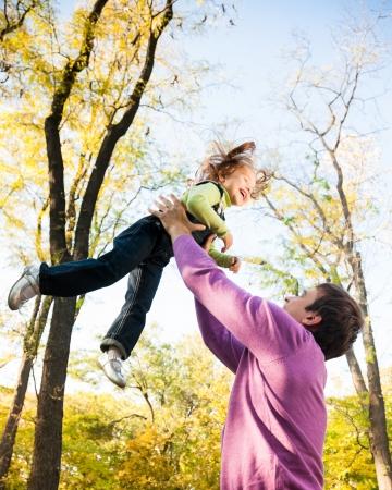 Man with child having fun in autumn park  Focus on man photo