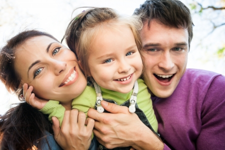 Low angle view portrait of happy smiling family in autumn  Focus on woman photo