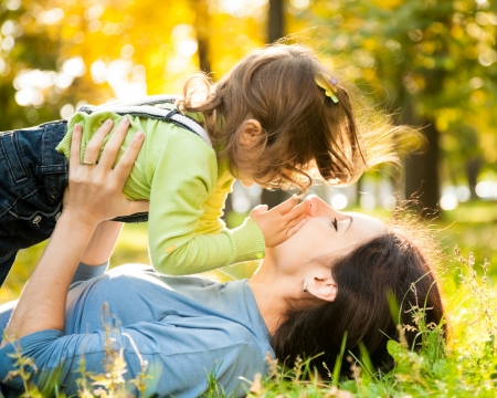 Happy family lying on grass in autumn park Stock Photo - 13881872
