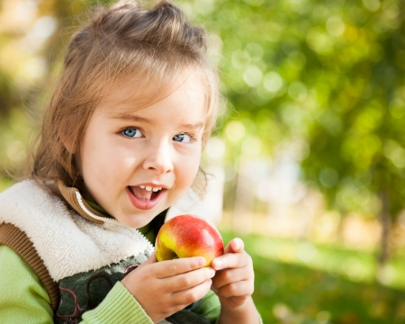 Closeup portrait of happy child eating red apple outdoors in autumn photo