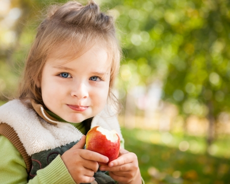 Portrait of happy child eating red apple outdoors in autumn photo