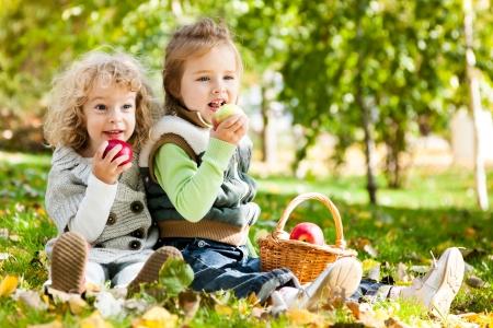 Children eating apples in autumn park  Family picnic