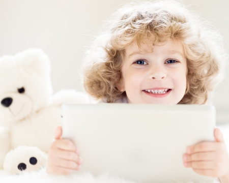 Portrait of happy child with toy using tablet computer photo