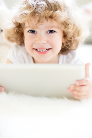 Portrait of happy child using tablet computer photo