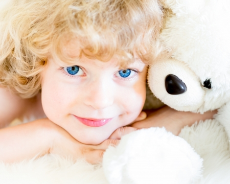 Happy child playing with a teddy bear photo