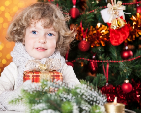 Happy child holding gift against Christmas tree with decorations photo