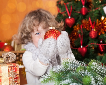 Happy child holding Christmas ball against decorated fir-tree photo