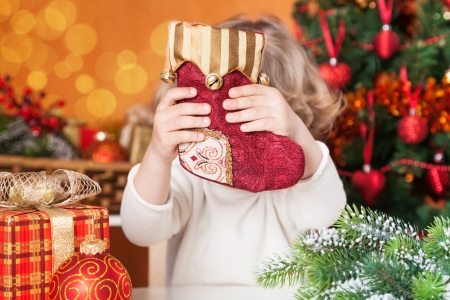 Funny child holding red sock against Christmas decorations background photo