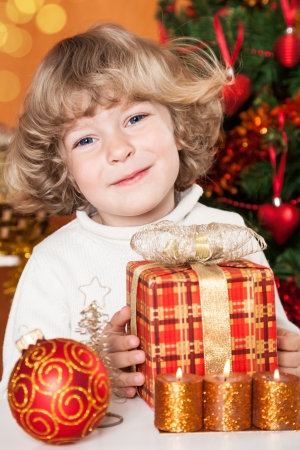 Smiling child holding present against Christmas tree with decorations photo