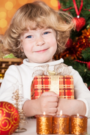 Happy child holding gift box against Christmas tree with decorations photo