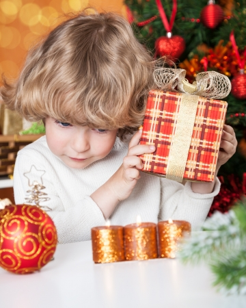Funny child holding gift against Christmas tree with decorations photo
