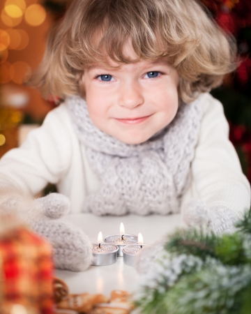 Smiling happy child with Christmas candles and decorations. Focus on candles photo