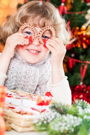 Funny smiling child holding handmade eco decorations against Christmas lights photo