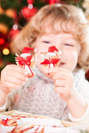 Happy child holding handmade eco decorations against Christmas lights photo