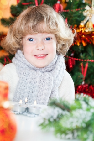 Portrait of funny smiling child against decorated Christmas background photo