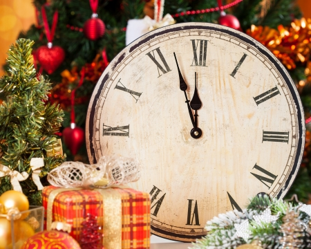 against the clock: Vintage wooden clock against Christmas tree decorations Stock Photo