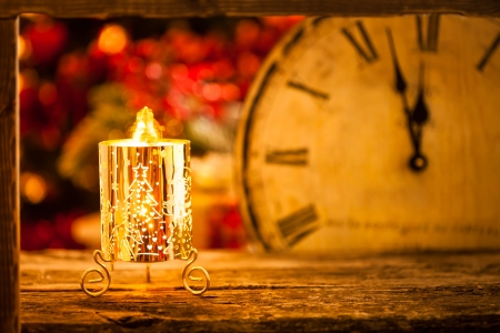 Christmas candle and vintage clock against lights blurred background photo