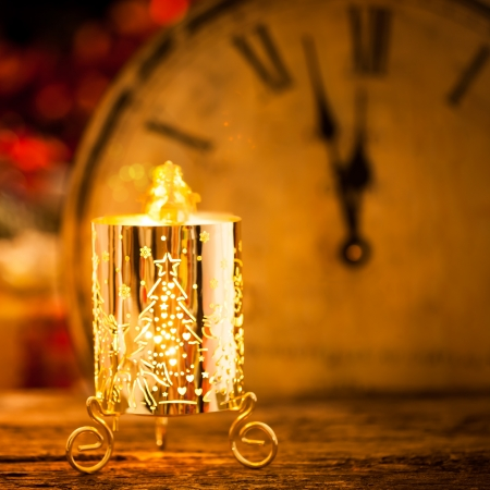 Burning Christmas candle against vintage clock. New year concept photo