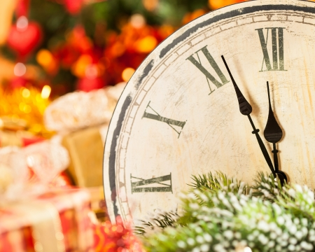 Vintage wooden clock against Christmas lights background. New year concept photo