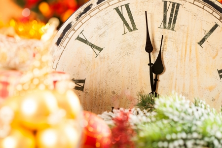 Old wooden clock against Christmas lightss. New year concept photo