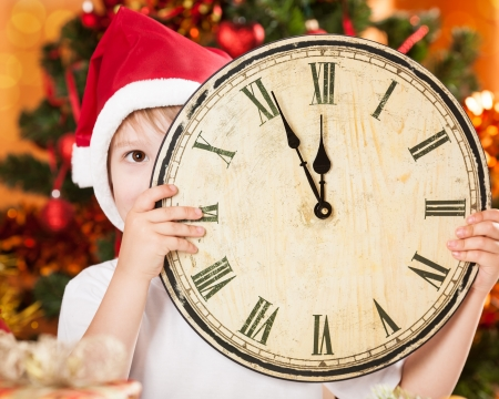 Funny kid hiding by vintage wooden clock agains decorated Christmas tree photo
