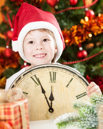 boy 12 year old: Happy kid in Santa s hat holding old wooden clock against decorated Christmas background