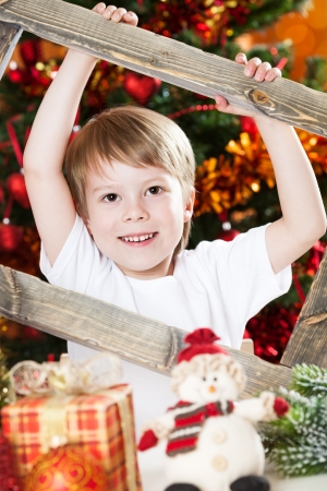 Happy boy holding wooden frame against Christmas lights background photo