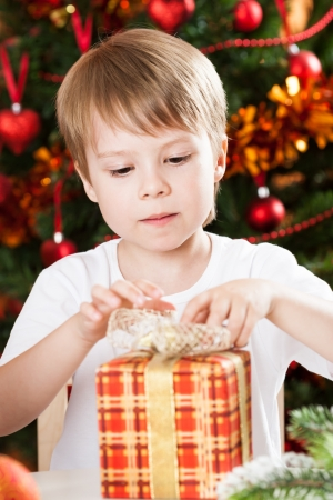 season opening: Surprised boy opening present against Christmas tree with decorations