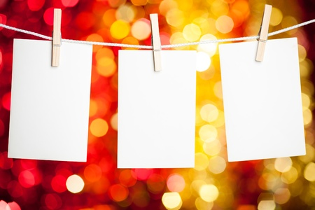 Blank paper cards hanging on clothespins against Christmas lights background photo