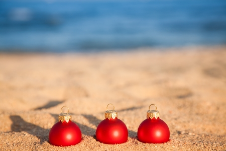 Christmas tree decorations on beach against blue sea Stock Photo