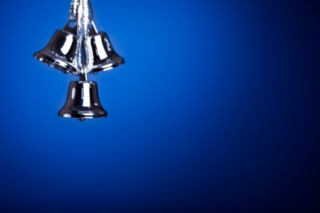christmas bells: Silver Christmas tree decoration against dark blue background Stock Photo