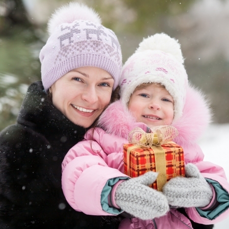 smile christmas decorations: Happy family with Christmas gift box in winter park Stock Photo