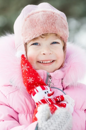 Happy smiling child with Christmas decoration in winter park photo